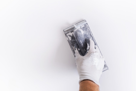 Hand of plasterer at wall polishing. House renovation concept. Stock Photo