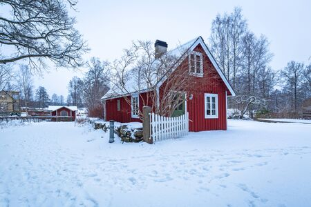 Winter scenery with red wooden house  in Sweden at dawn