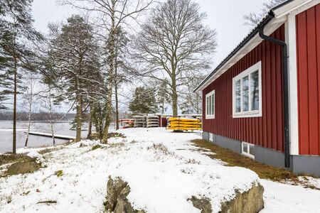 Snowy winter scenery with red wooden house in the forest, Sweden