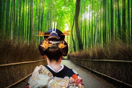Donna in kimono tradizionale a piedi nella foresta di bambù di Arashiyama, Japan