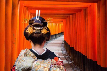 Woman in traditional kimono walking at torii gates, Japan