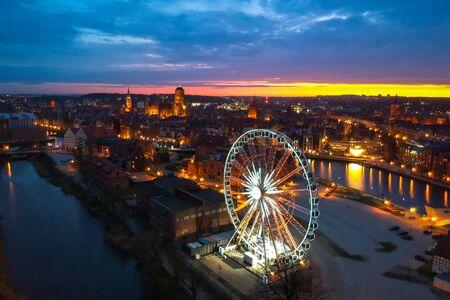 Sunset over the Gdansk city with illuminated ferris wheel, Poland