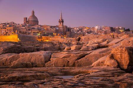 Rocky coast of Malta and the architecture of Valletta city at dawn.