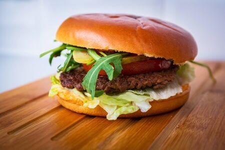 Homemade hamburger on wooden cutting board Foto de archivo