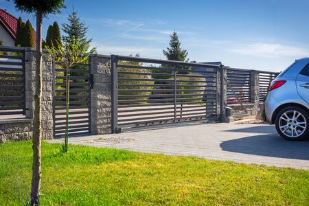 Stone fence and entrance gate with remote control Stockfoto
