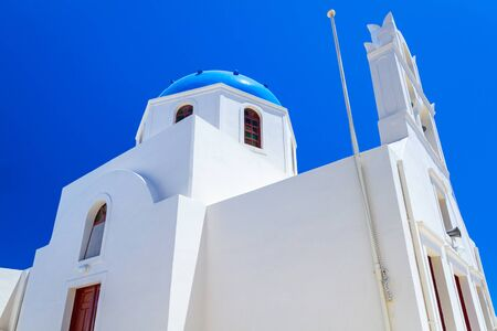 White church with blue dome in Oia town on Santorini island, Greece