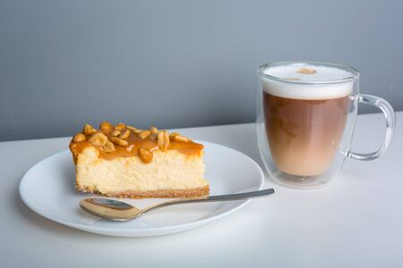 Latte coffee with a piece of cheesecake with caramel and peanuts coating