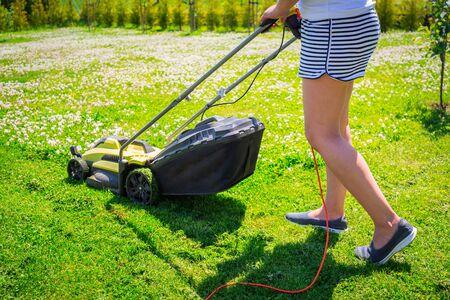 Woman cutting grass in her yard with lawn mower. Фото со стока