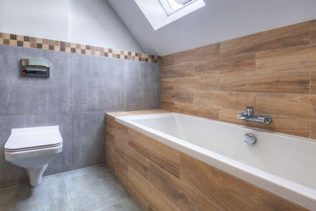 New bathroom interior in the house. Gray concrete tiles with wooden decor. Banque d'images
