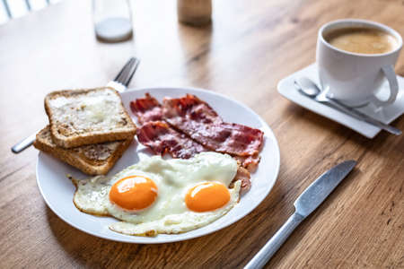 Tasty breakfast with two eggs, bacon, toasts and coffee