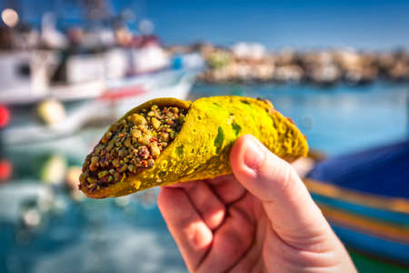 Maltese pistachio cannoli in hand at the fishing port of Marsaxlokk