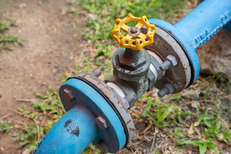 stop gate valve: Yellow valve opening and closing pipelines. Stock Photo