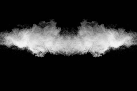 Freeze motion explosion of white dust on a black background.Stopping the movement of white powder on dark background. Imagens