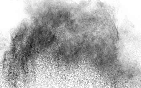 Closeup of black dust particles explode isolated on white background Stock Photo