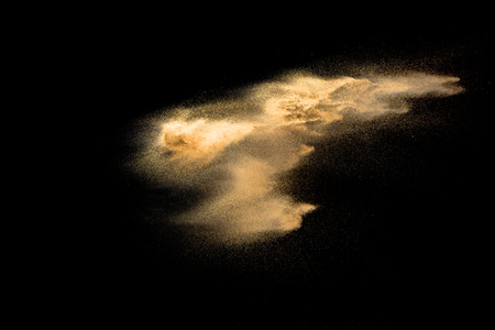 Golden sand explosion isolated on black background. Abstract sand cloud. Golden colored sand splash against dark background. Yellow sand fly wave in the air. Banque d'images - 115992430