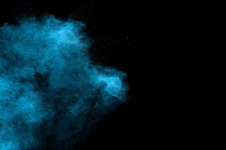Blue dust explosion on black background. Freeze motion of color powder splash.