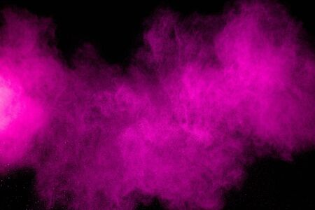 Pink dust particles splash on black background.Pink powder splash. 스톡 콘텐츠