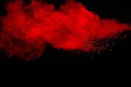 Red particles explosion on black background. Freeze motion of red dust splash.