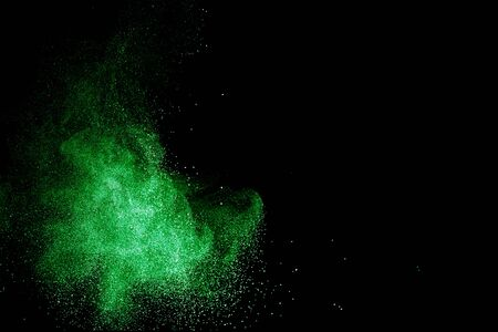Green color powder explosion cloud on black background.Green dust splash.