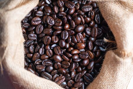 Brown roasted coffee beans with Burlap Sack. 스톡 콘텐츠
