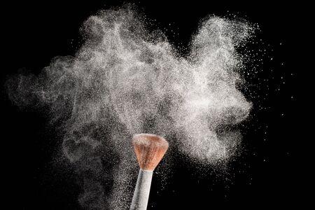 White powder splash with make up brush blusher isolated on black background.