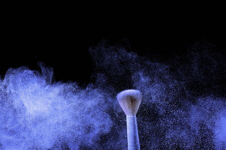 Make-up brush with blue powder splash cloud.