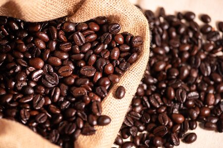 Brown roasted coffee beans in burlap Sack.Roasted coffee beans texture, used as a background. 스톡 콘텐츠