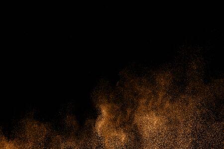 Abstract explosion of orange dust on black background.Freeze motion of orange powder splashing.