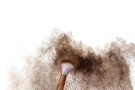 Brown powder dust cloud.Brown particles splattered on white background. Stock Photo