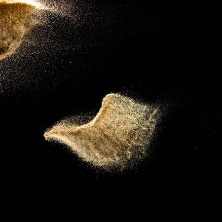 Dry river sand explosion.Brown color sand splash against black background.