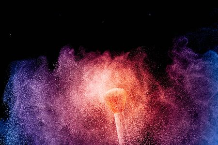 Make-up and beauty concept. Brush with orange blue powder explosion on black background