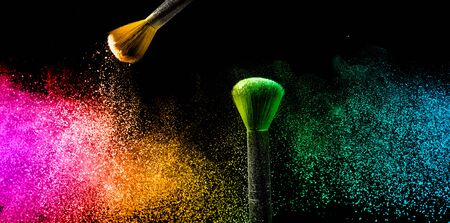 Two brushes with pastel make up powder impact to make a colorful cloud.