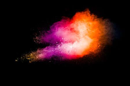 Explosion of colorful pigment powder on black background.Vibrant color dust particles textured background. Foto de archivo