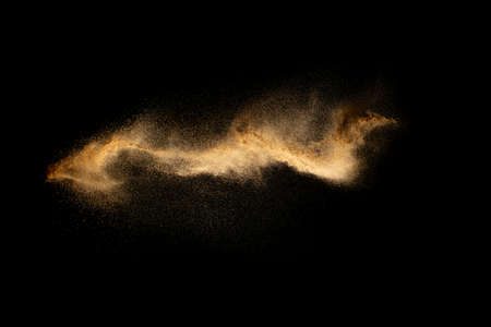 Abstract motion blurred brown sand background.Sandy explosion isolated on over dark background.