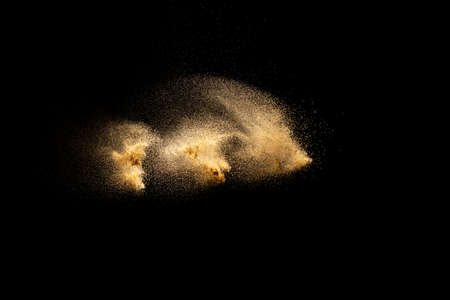 Golden sand explosion isolated on black background. Abstract sand cloud. Golden colored sand splash against dark background. Yellow sand fly wave in the air. Foto de archivo - 152503540