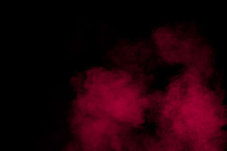Abstract red powder dust explosion on black background.