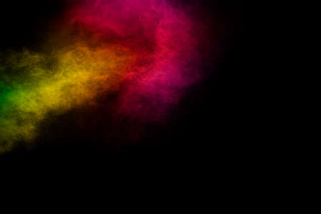 Explosion of colorful pigment powder on black background.Vibrant color dust particles textured background. Archivio Fotografico