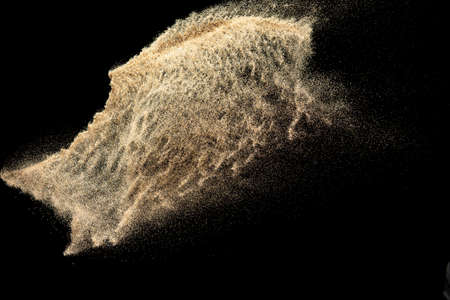 Brown colored sand splash.Dry river sand explosion isolated on black background.