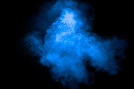 Blue color dust particles explosion cloud on black background.Color powder splash. 免版税图像