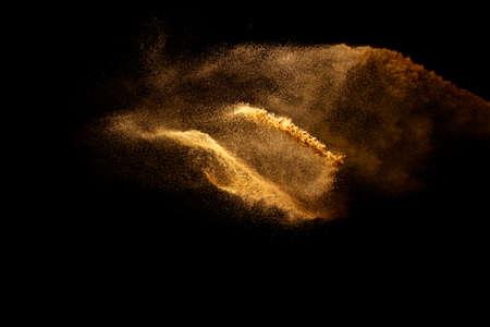 Abstract motion blurred brown color sand splash against black background.