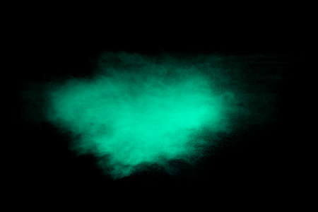 Green dust particles explosion on black background. Color powder dust splash.