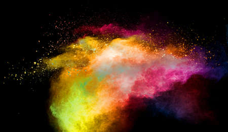 Multicolored powder explosion on black background.Colorful red yellow splash cloud on background.