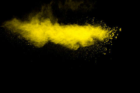 Yellow dust particles explosion on black background.Yellow powder  splash. Foto de archivo