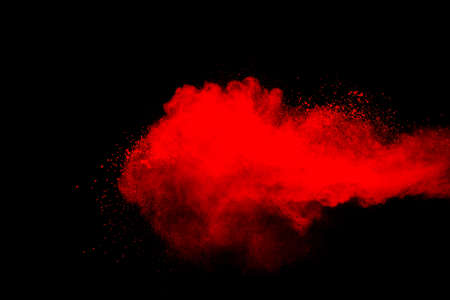 Red powder explosion cloud on black background. Freeze motion of red color dust  particles splashing.