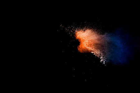 Orange blue color powder explosion on black background.