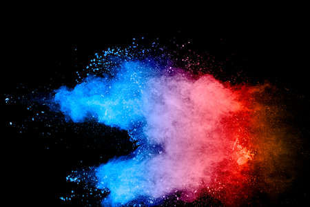 Multicolored powder explosion on black background. Blue pink and orange dust splashing.