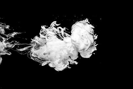White ink in water, isolated on black background. Acrylic paint splash.
