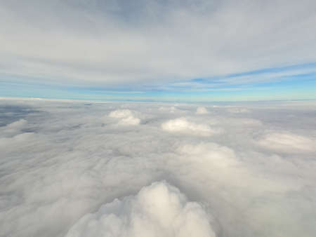 Arial view from internal cabin of aeroplane.Clouds in the sky and cityscapes though airplane window.
