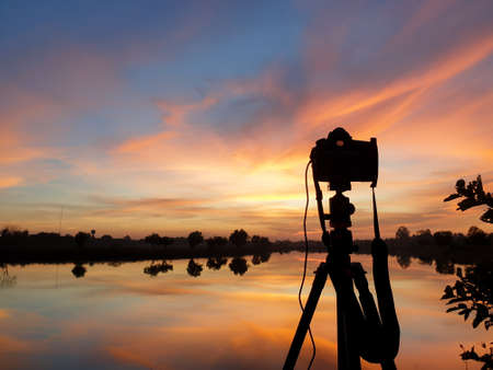 Silhouette of a camera at sunset.Dslr camera shooting on a cityscape sunset with lake reflection. 免版税图像