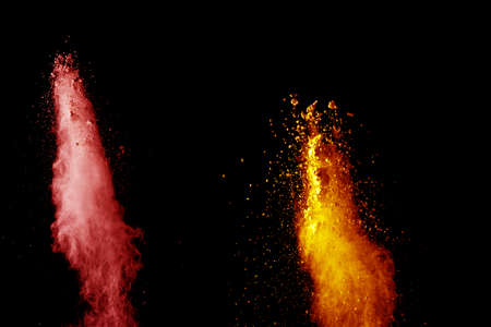 Red orange color powder explosion cloud isolated on black background.